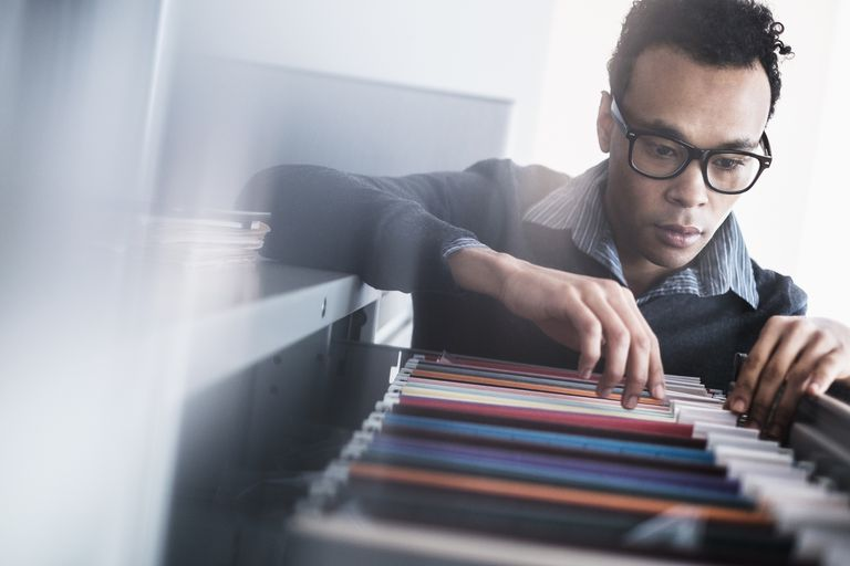 Mid adult man searching for files in filing cabinet