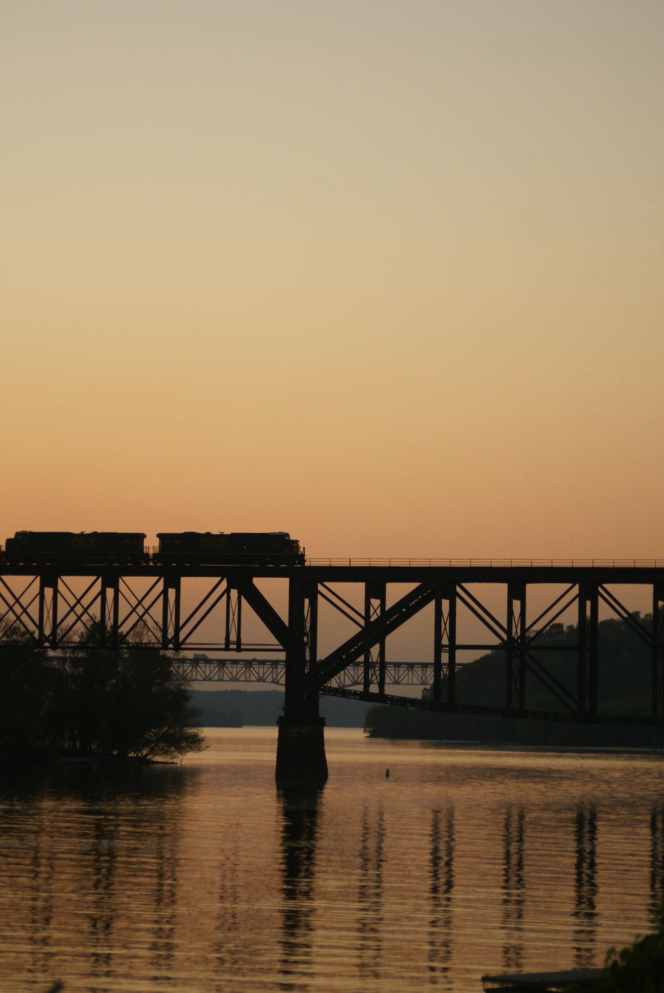 Train crossing a river at sunset.