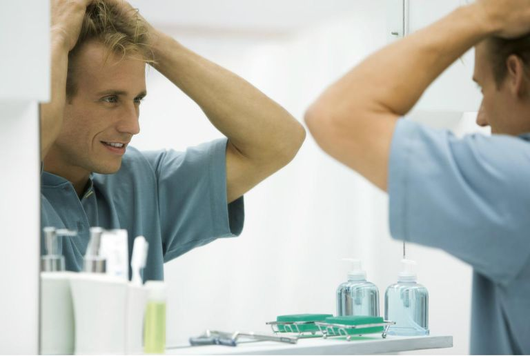 Man looking at self in mirror, fixing hair