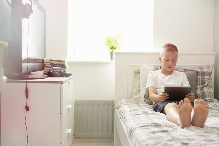 Boy using tablet on his bed