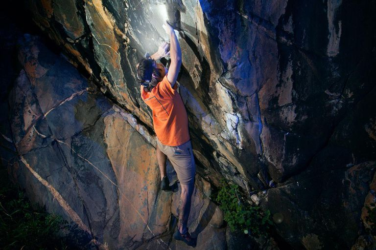 Men bouldering at night with a headlamp on.