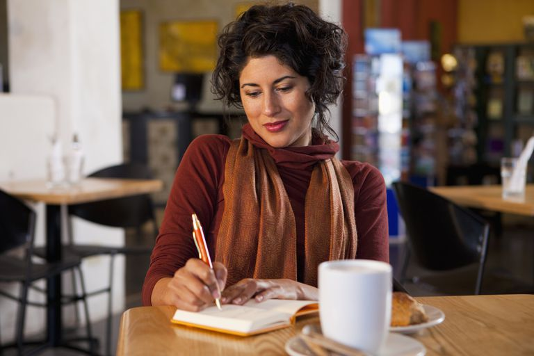 woman writing in journal in cafe