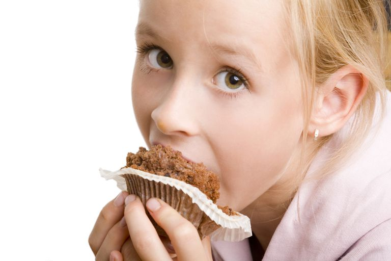 Girl eating muffin for after-school snack