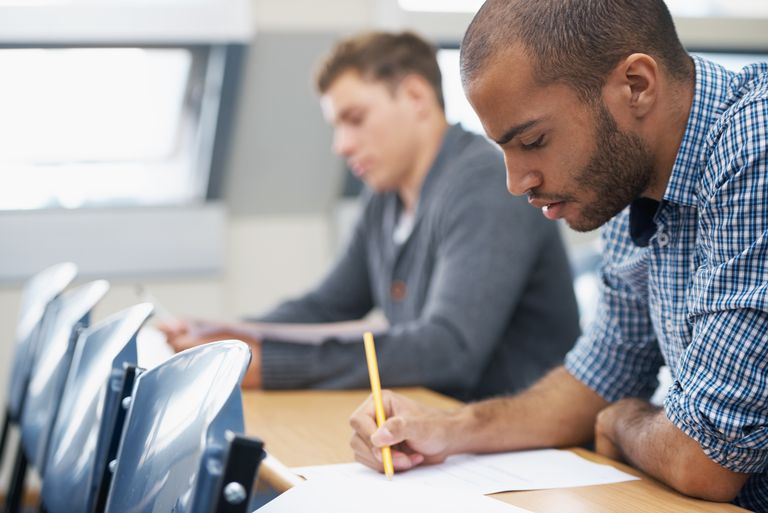 Two male students writing exam in a lecture hall