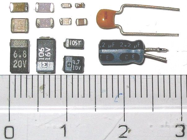 Examples of types of capacitors including surface mount and through-hole styles. Materials include multi-layer ceramic, aluminum organic polymer or film bottom, tantalum, and electrolytic capacitors.