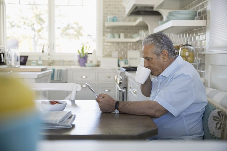Senior man drinking coffee and using digital tablet at breakfast nook
