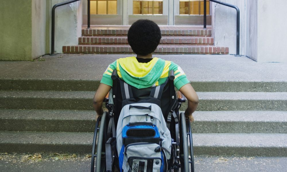 A disabled student in front of his school.