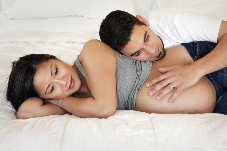 Pregnant woman laying on bed, husband's head resting on her with hand on her abdomen