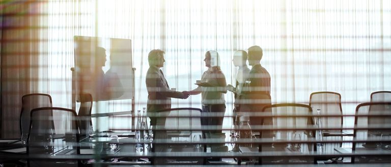 Business people standing in conference room shaking hands