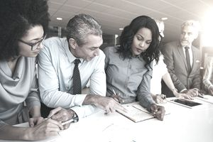 Multiracial workers discussing papers sitting in office