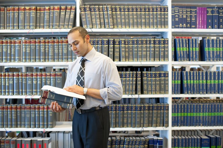 Businessman reading book in law library