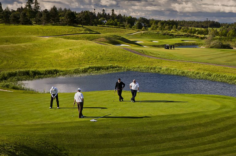 View of the people golfing near a water hazard at the second hole on the PGA Course at Gleneagles Golf Resort in Scotland