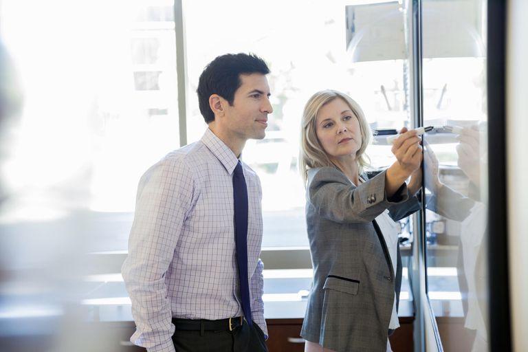 Businesswoman writing on whiteboard in boardroom.