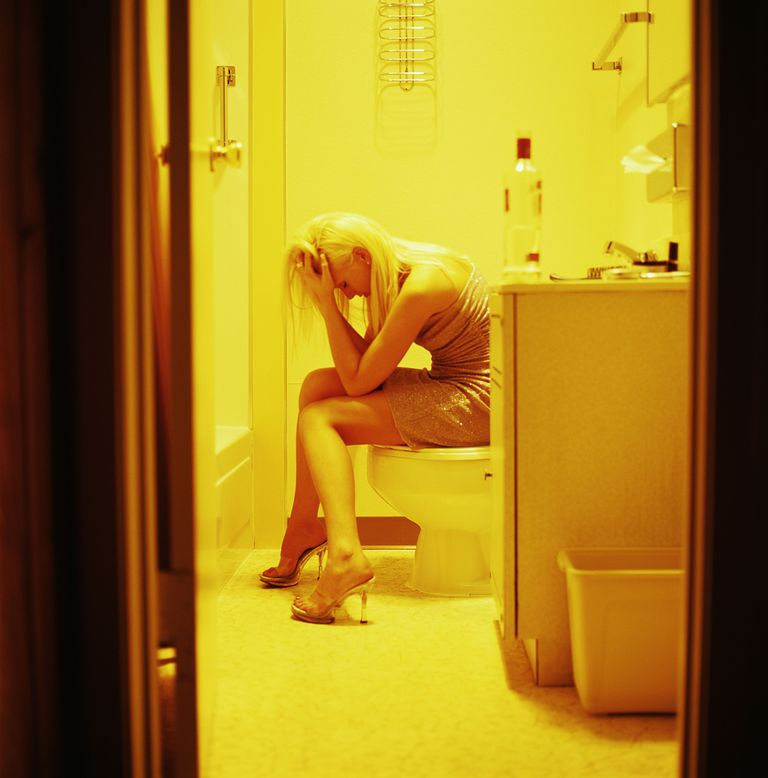 Woman sitting in the bathroom at a party.