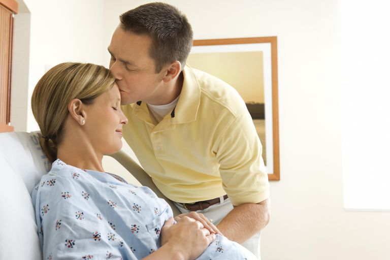 Husband kissing pregnant wife in hospital