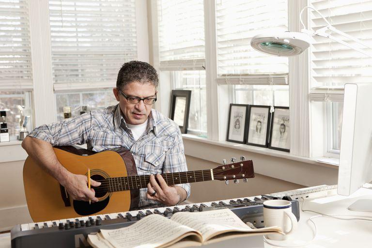 Hispanic man composing music on guitar