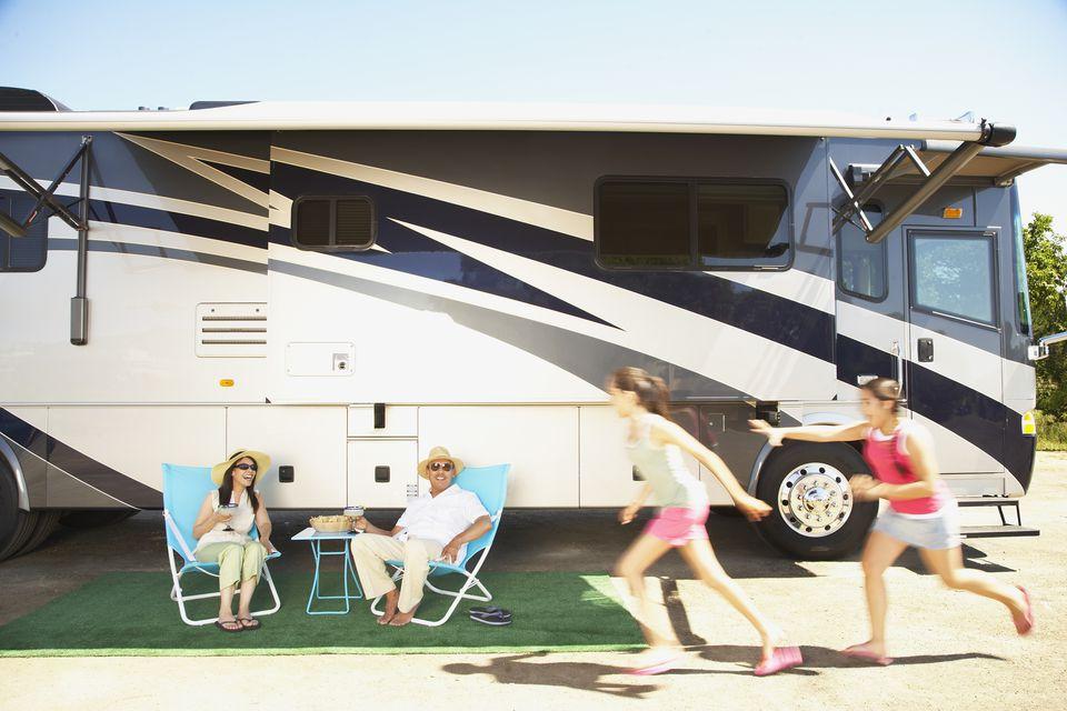 Hispanic family relaxing next to recreational vehicle