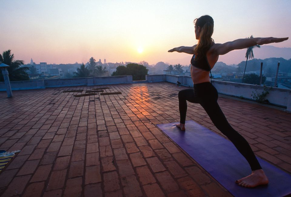 India, Mysore, woman practising yoga on roof.