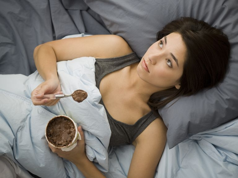 Woman lying down in bed spilling chocolate ice cream on blanket
