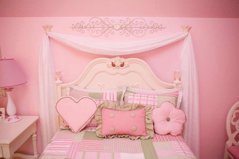Pink girl's room with simple swag canopy suspended from hooks.