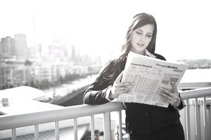 Business woman reading the financial section of a newspaper. Seattle skyline in the background.