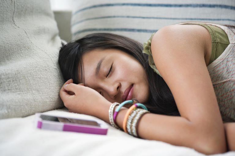 Teenage girl (13-14) asleep on sofa