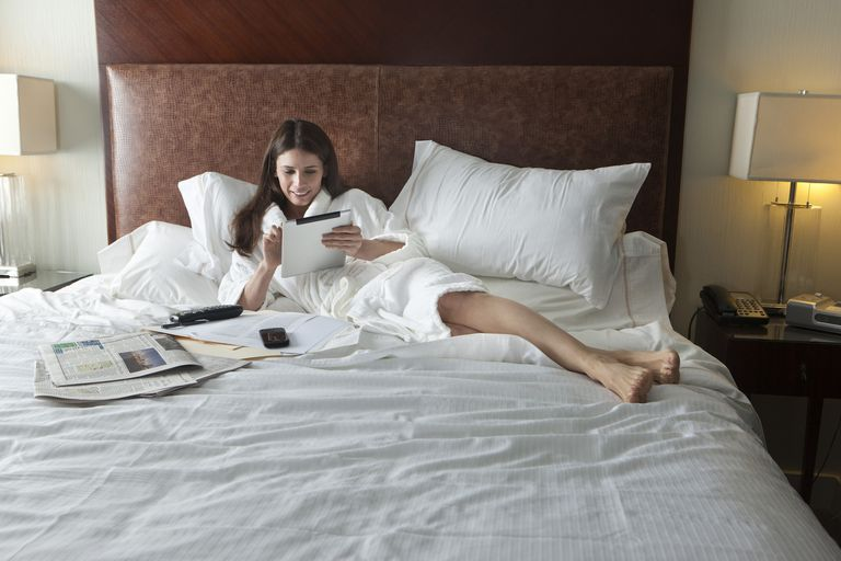 Woman relaxing and reading digital tablet in bed