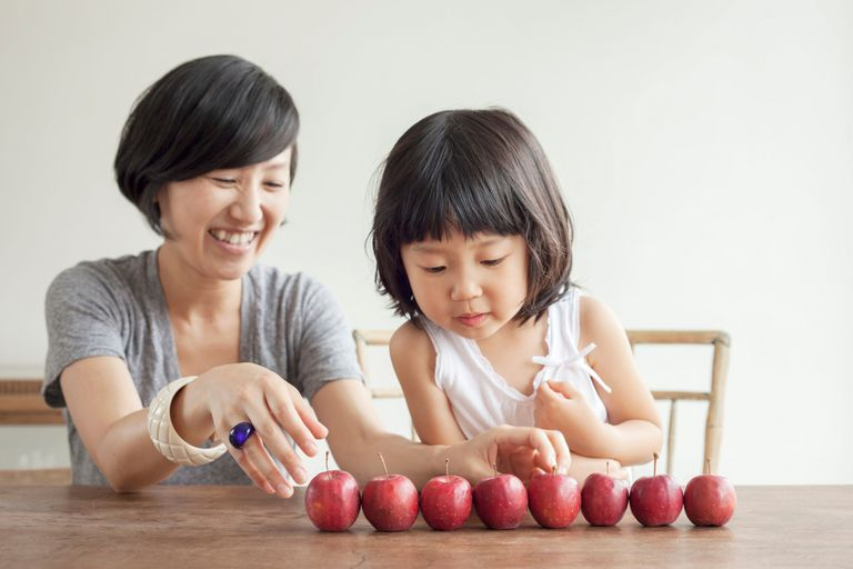 Mother and daughter with red apples in a row