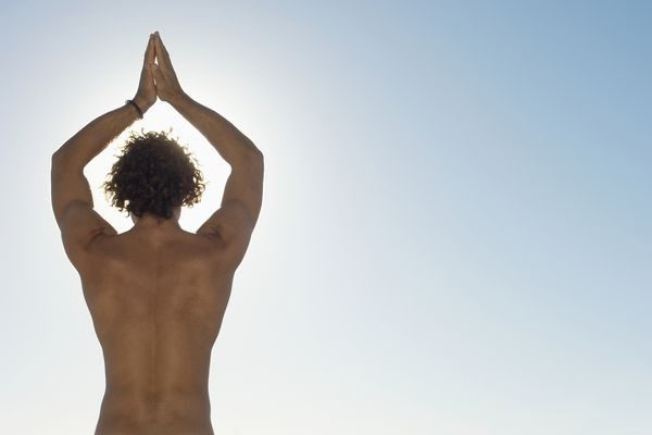 View of man practicing yoga from behind