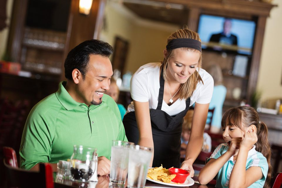 Father and daughter receiving food in restaurant