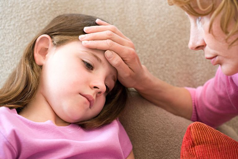 A mother checking her daughter's forehead to see if she has a fever