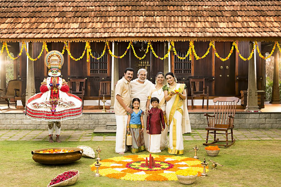 South Indian family standing near rangoli of flowers during Onam