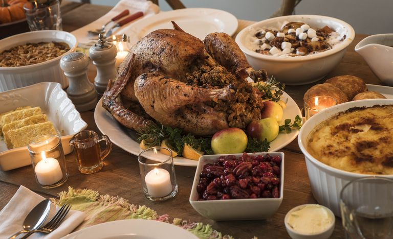 Image of a turkey on a dining room table surrounded by sides