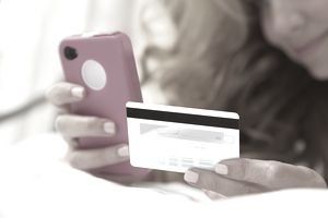Woman using smartphone with credit card