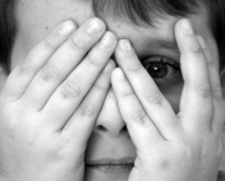 Young boy peeking from between his fingers