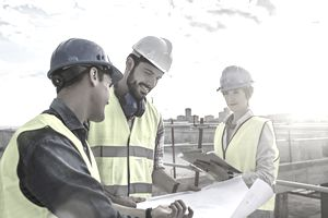 Construction workers looking at blueprints on construction site