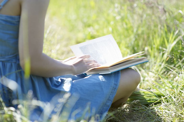 Close up of woman reading book in countryside.