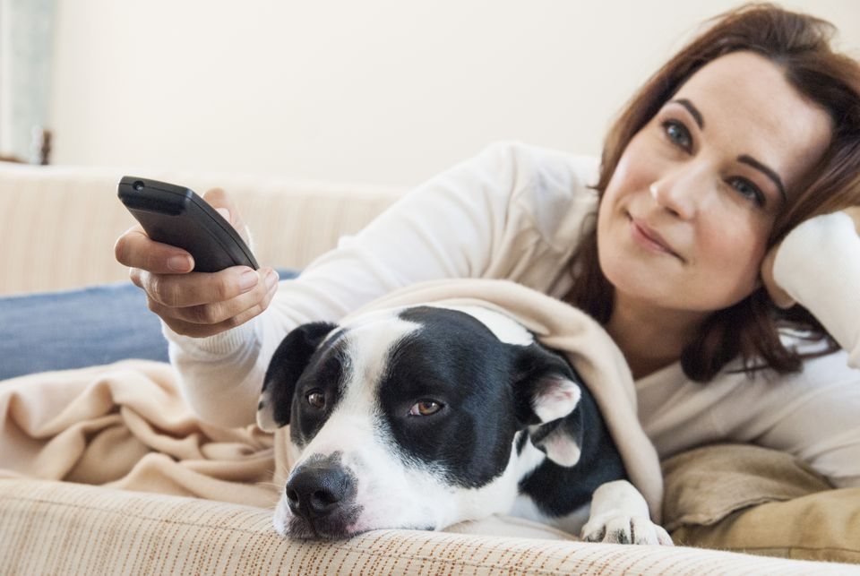 Woman watching television with dog