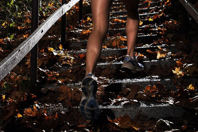 Young woman climbing stairway in forest, low angle view