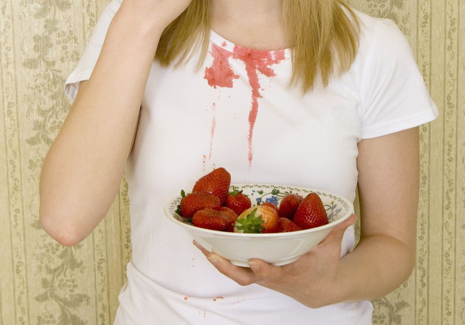 Young woman eating strawberry and spilling juice on t-shirt