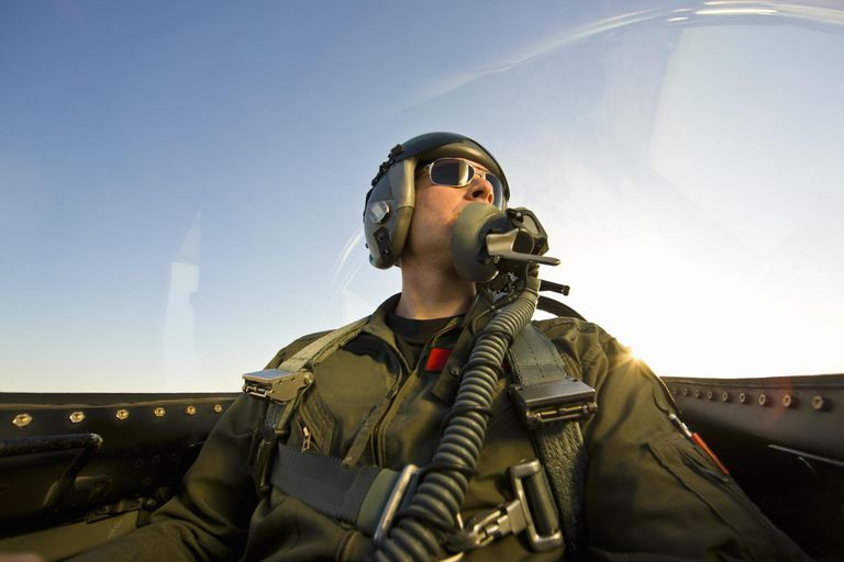 Fighter pilot in cockpit of F-16 fighter jet. Front view of pilot with flight suit and helmet.