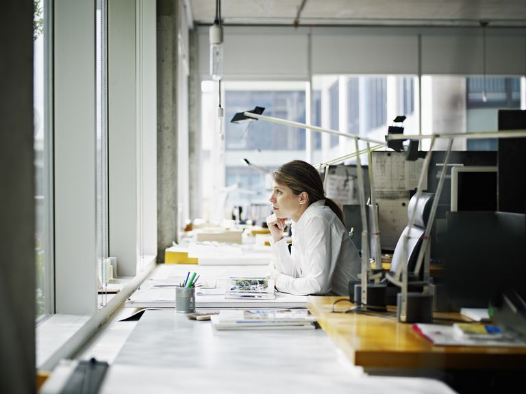 Architect sitting at desk looking out window