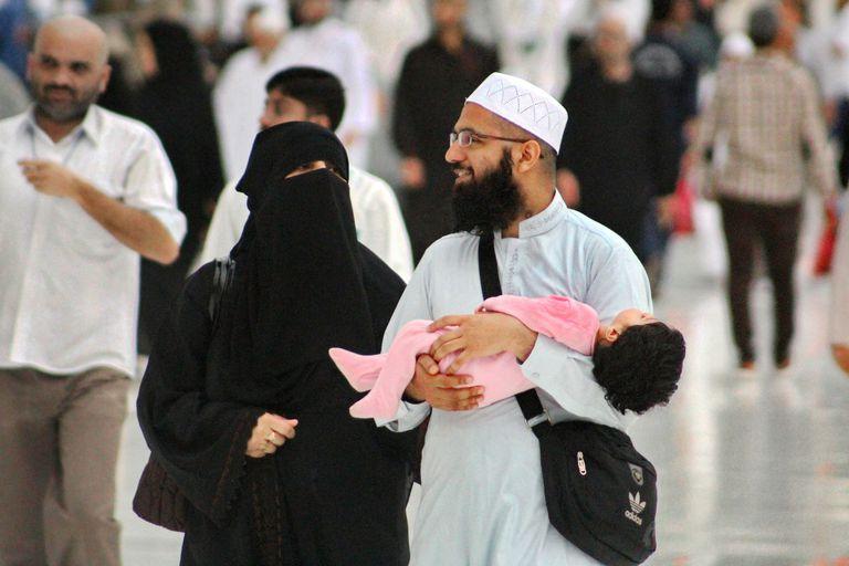 A young Muslim couple and their toddler at Masjid al-Haram, Makkah, Saudi Arabia.