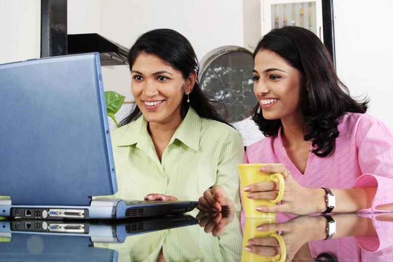 A mother with her daughter working on laptop