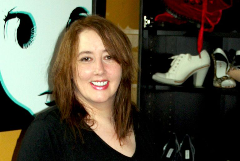 Shoes expert Desiree Stimpert standing in front of collection of footwear.