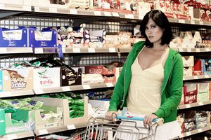 Young woman standing in a supermarket in front of a shelf with sweets