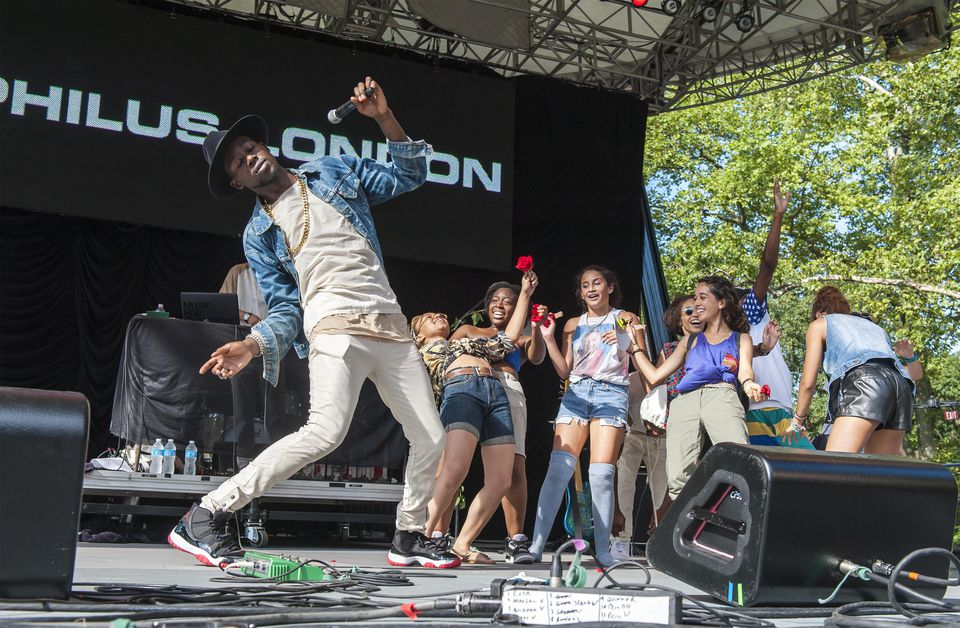 Trinidad-born, Brooklyn-bred Rapper/MC Theophilus London closes his set with young fans from the audience on stage at Central Park SummerStage, New York, New York, August 4, 2012.