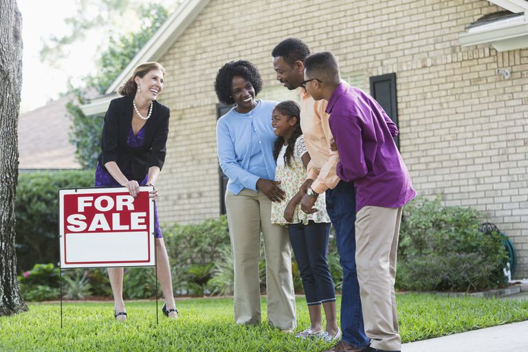 family outside home for sale with real estate agent