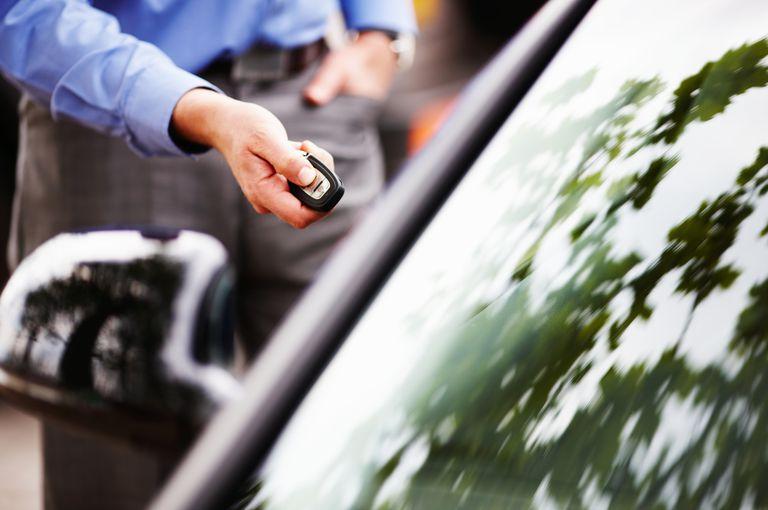 Man using keyless remote to unlock car