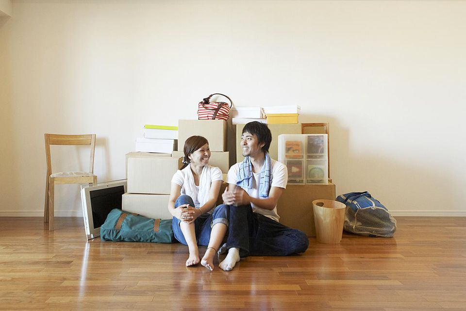 Happy couple sitting on the floor with packed moving boxes